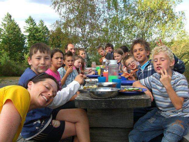 Gruppenbild von Kindern beim Mittagessen im Freien